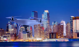 Drone quad copter with camera flying towards the city center in night Stock Images