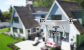 Drone quad copter with camera spying on the house and yard.  Stock Photography