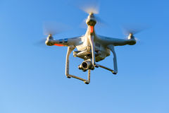Drone quad copter with digital camera flying in blue sky Royalty Free Stock Photo