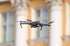 Drone quad copter is flying against the background of windows and columns of an ancient building. Stock Photos