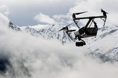 drone quad copter with high resolution digital camera flying over the snowy mountain royalty free stock image