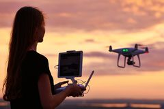 Drone quadcopter with digital camera operated by woman at sunset royalty free stock photography