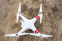 Drone quadcopter on a dirt road, getting ready to take off. Top view, flat lay composition royalty free stock image