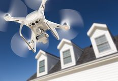 Drone Quadcopter Flying, Inspecting and Photographing House. Drone Quadcopter Flying, Inspecting and Photographing Roof of a House stock photography