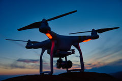 Drone quadrocopter with digital camera at sunset Stock Image