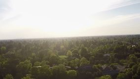 Drone Rapid 360 Degree Turn Over Trees And Suburbs stock footage
