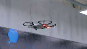 Drone with red light flying indoor. Under ceiling at robot technology exhibition. Future concept stock video footage