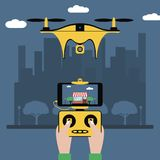 Drone and remote control. Hands hold a radio controller with screen to quadcopter flying over city. Quadricopter with a camera. Stock Photography
