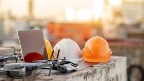 Drone, remote control, laptop and helmet at construction site. Drone, remote control, smartphone, laptop computer and protective helmet at construction site royalty free stock photography