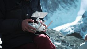 Drone Remote Controlling. Hand and remote view of a drone pilot operator. A traveler in the snowy mountains takes. Pictures and examines the territory stock footage