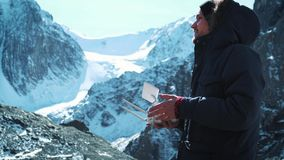 Drone remote controlling. Hand and remote view of a drone pilot operator. A traveler in the snowy mountains takes. Pictures and examines the territory stock video footage