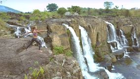 Drone removes from girl changing yoga pose by waterfall stock footage