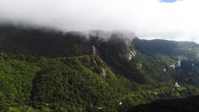 Aerial view in the clouds of Adam Peak in Sri Lanka in sunny day. The drone removes the mountainous terrain of Adam Peak in Sri Lanka under the cover of clouds stock footage