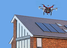 Drone repair surveillance. Photo of a drone with video camera being used to survey rooftop construction or damage and repairs in hard to get to places Stock Photos