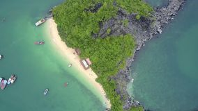 Drone Rises above Tranquil Azure Bay and Rocky Island. Drone rises above rocky island covered with tropical forest and sand beach in tranquil azure bay and stock video