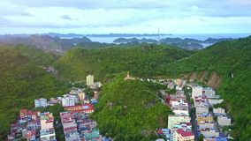 Drone Rises above Town with Landmark on Hill Top. Drone rises above nice pictorial resort town and religious landmark on green hill top at sunset twilight stock video footage
