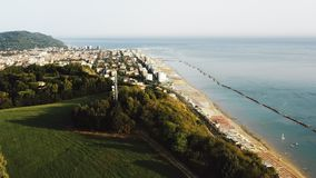 Drone rising above green tree mountain hill with epic sea view to reveal small sunny bay town panorama in Pesaro Italy. Peaceful summer Mediterranean shore stock video footage