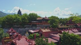 Drone Rotates above Temple Territory among Tropical Plants Sky. Drone rotates above religious temple territory in oriental style among tropical plants and sky stock video