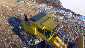 The drone shooting of the working bulldozers at the city landfill. 4K. The drone shooting of the working bulldozers at the city landfill stock video footage