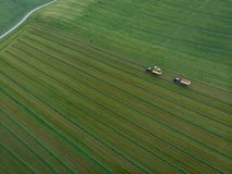 Drone shot of agricultural field with tractors harvesting hay royalty free stock images