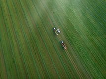 Drone shot of agricultural field with tractors harvesting hay royalty free stock photos