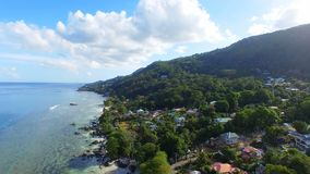 Aerial view of ocean and houses on the beach on tropical island, Seychelles 1. Drone shot of Beau Vallon Beach, ocean and houses on the beach on tropical island stock video