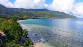 Aerial view of ocean, beach and mountains on the tropical island, Seychelles 8. Drone shot of Beau Vallon Beach, ocean and mountains on the beach of tropical stock video footage