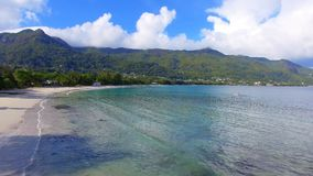 Aerial view of ocean, beach and mountains on the tropical island, Seychelles 2. Drone shot of Beau Vallon Beach, ocean and mountains on the beach of tropical stock video footage