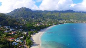 Aerial view of ocean, beach and mountains on the tropical island, Seychelles 9. Drone shot of Beau Vallon Beach, ocean and mountains on the beach of tropical stock footage