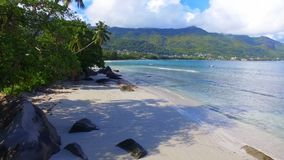 Aerial view of ocean, beach and mountains on the tropical island, Seychelles 7. Drone shot of Beau Vallon Beach, ocean and mountains on the beach of tropical stock footage