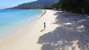 Aerial view of a beautiful girl walking down the Beau Vallon Beach 3, Seychelles. Drone shot of a beautiful girl walking down the Beau Vallon Beach , Seychelles stock footage