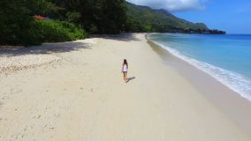 Aerial view of a beautiful girl walking down the Beau Vallon Beach 6, Seychelles. Drone shot of a beautiful girl walking down the Beau Vallon Beach , Seychelles stock video