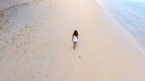 Aerial view of a beautiful girl walking down the Beau Vallon beach 4, Seychelles. Drone shot of a beautiful girl walking down the Beau Vallon Beach , Seychelles stock footage