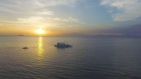 Aerial: Beautiful Tropical Sea Sunset Landscape. Drone Shot Of Beautiful Tropical Sea Sunset With People Rowing At Summer stock footage