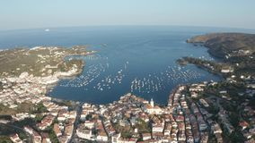 Drone shot of blue bay with yachts near Cadaques. Aerial shot of Spanish town Cadaques on Cap de Creus peninsula against beautiful bay with anchored yachts stock video