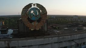 Drone shot of emblem on building`s roof in Pripyat. Close-up of big rusty emblem of Soviet Union in Pripyat town at sunrise, Chernobyl exclusion zone. Aerial stock footage