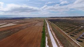 Drone shot of field of solar panels. Aerial footage following industrial company truck riding through gravel offroad road near field of solar panels producing stock video