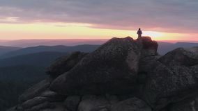 Drone shot of lonely man standing on top of a mountain and enjoying the sunset. HD stock video footage