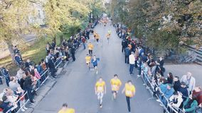 Drone shot of people in orange shirts running marathon in city park
