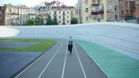 Drone shot of plus size female jogging at stadium. Back drone flight over stadium track where overweight female runner in sportswear exercising early morning stock video