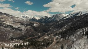 Drone shot of scenic landscape of the rocky mountains, forests and snowy back roads near Aspen Colorado stock footage