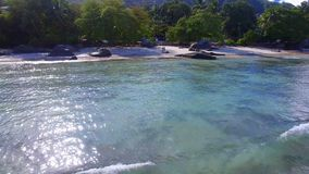 Aerial view, fly away of the shore 1, Beau Vallon Beach, Mahe Island, Seychelles. Drone shot of the shore of Beau Vallon Beach, ocean and mountains on the beach stock video footage