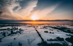 Drone shot of the sky. Sunset clouds land trees landscape snow Stock Images