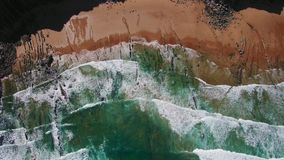 Drone shot of waves rolling on shore. Dramatic and epic aerial shot of coastal line of northern rocky beach, surfing banks waves overtaking sand and crashing on stock footage
