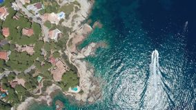 Drone shot of yacht sailing in sparkling sea water. Aerial shot of motor yacht leaving white foamy trail while sailing through clear blue water of Cala d`en stock footage