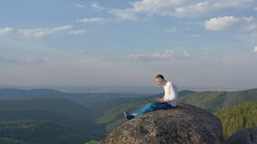 Drone shot of a young male freelancer sitting on top of a mountain and working on a laptop.