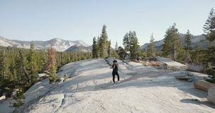 Drone shot of young woman taking a photo with professional camera at amazing mountain scenery in Yosemite national park. Female photographer and journalist at stock footage