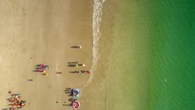 Teachers gather children into group on beach ocean waves roll. Drone shows from above how teachers gather children into group on beach and transparent azure stock footage