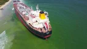 Drone Shows Aground Tanker in Shallow Water against Desert Coast. Drone shows huge modern tanker aground in ocean shallow water after typhoon against desert stock video footage