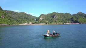 Drone Shows Asian Fishermen in Wooden Boat and Mountain. Drone shows asian fishermen in wooden boat on ocean water and large mountain island covered with deep stock footage